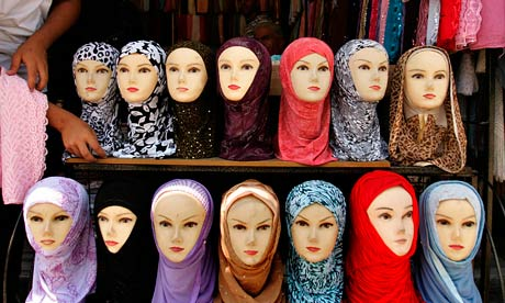 Jordanian vendor arranges headscarves for sale, in downtown Amman