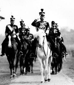 Emperor Hirohito salutes from his mount, his favorite white horse, during a military review in Tokyo